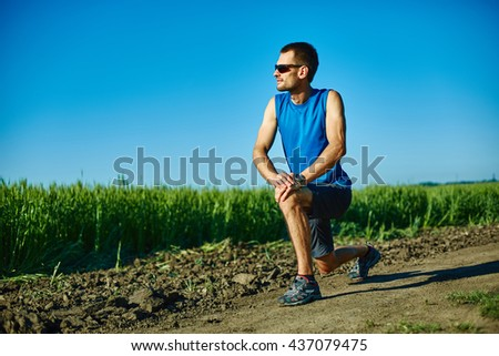 man runner athlete warming up before jogging along a green field in the early morning. man lunged forward on one knee. man fitness sunset jogging workout wellness concept. free space in front of the