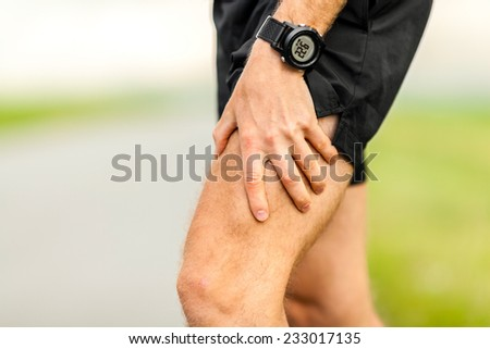 Man runner holding painful leg and muscle on running training outdoors in summer nature, sport jogging physical injury when working out, pain. Health and fitness concept with sore body - stock photo