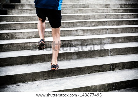 Man runner running on stairs in city, sport training. Young male athlete training and doing workout outdoors in city. Fitness and exercising outdoors urban environment. - stock photo