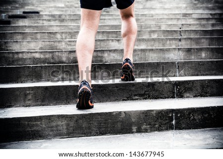 Man runner running on stairs in city, sport training. Young male jogger athlete training and doing workout outdoors in city. Fitness and exercising outdoors urban environment. - stock photo