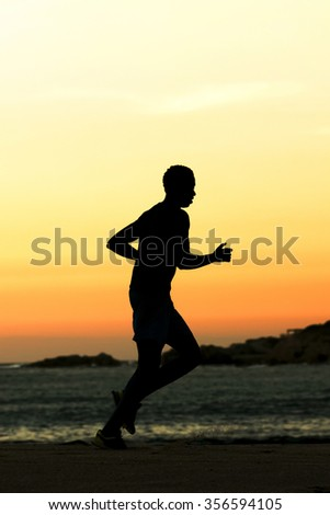 man runner silhouette  in the beach shore at sunset - stock photo