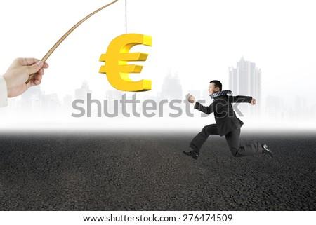 Man running after 3D golden euro symbol bait on fishing rod hand holding, with  asphalt road urban scene background - stock photo
