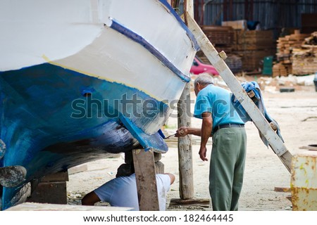 man running and boat paints. old port worker repairing a boat - stock photo