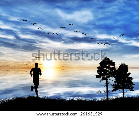 man running by the lake under clouds of colors - stock photo