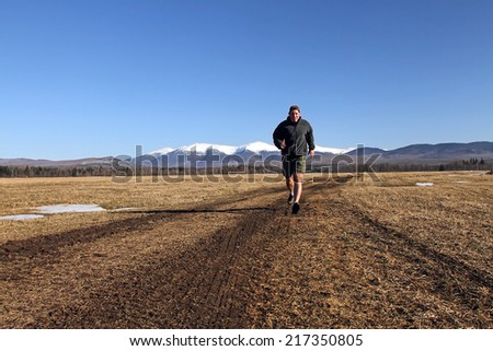 Man running during the spring with New Hampshire White Mountains in background. - stock photo
