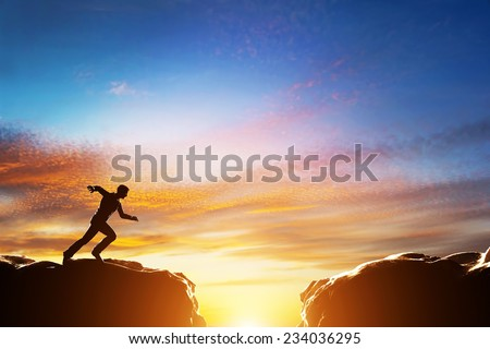 Man running fast to jump over precipice between two mountains. Concepts of determination, business, challenge, success, risk etc. - stock photo