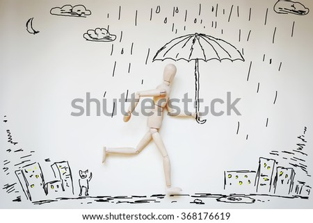 Man running home under umbrella in raining. Abstract image with wooden puppet - stock photo