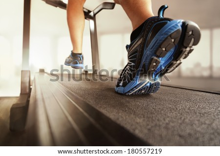 Man running in a gym on a treadmill concept for exercising, fitness and healthy lifestyle - stock photo