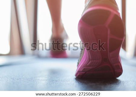 Man running in a gym on a treadmill concept for exercising, fitness and healthy lifestyle. - stock photo