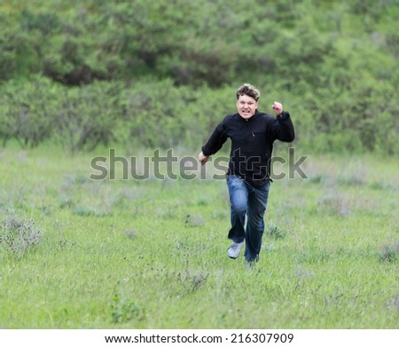 man running in a meadow - stock photo