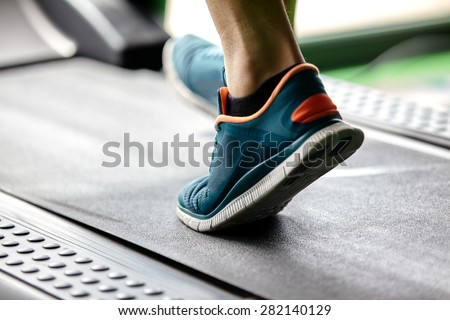 Man running in a modern  gym on a treadmill concept for exercising, fitness and healthy lifestyle - stock photo