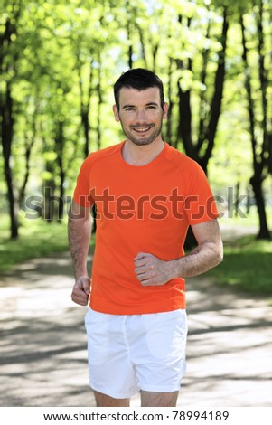 man running in a park in spring - stock photo