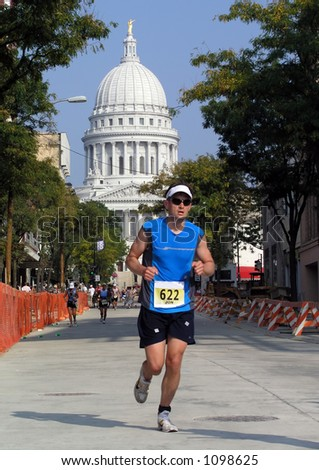 Man running in a triathlon in front of the Capitol building, Madison, Wisconsin - stock photo