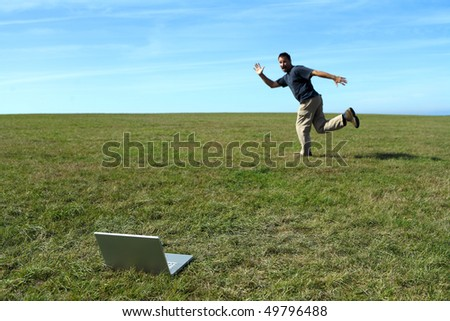Man running in field near laptop - stock photo