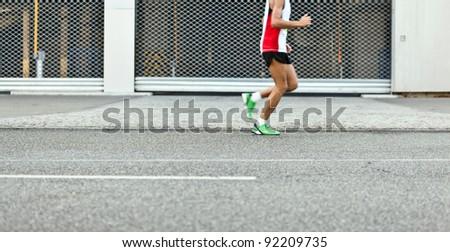 Man running in marathon on city street, motion blur - stock photo