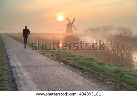 Man running in the foggy countryside near a windmill during a tranquil sunrise. Shallow D.O.F.