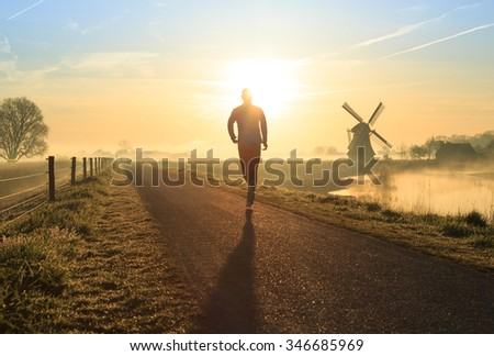 Man running in the foggy, Dutch countryside near a windmill. - stock photo