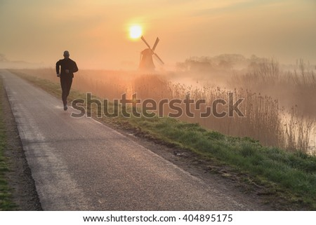 Man running in the foggy, Dutch countryside near a windmill during a tranquil sunrise. Shallow D.O.F. - stock photo