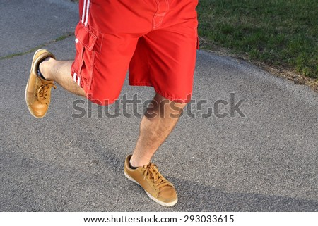man running legs in park, leather shoes, red shorts