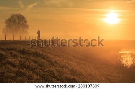 Man running on a dike in the foggy, Dutch countryside. - stock photo
