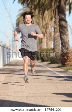 Man running on a path with palms. Front view