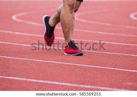 Man running on a running track in the stadium.  - Use For fitness or competition.