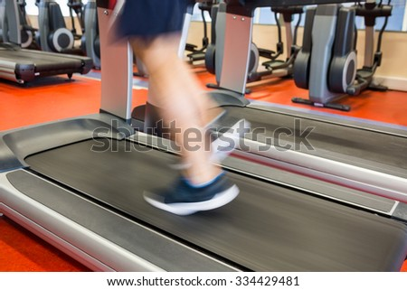Man running on a treadmill at the gym