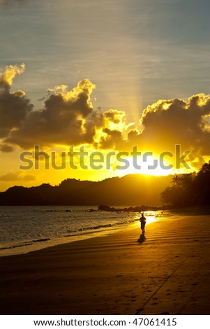Man running on beach at evening - stock photo