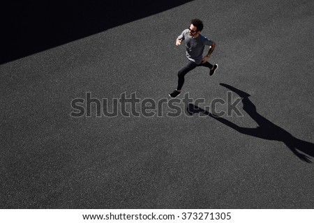 Man running on country road, healthy inspirational fitness lifestyle, sport motivation speed interval training. Runner jogging training and doing workout exercising power walking outdoors in city. - stock photo