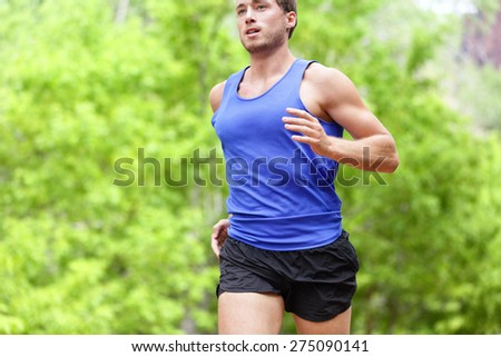 Man running on road. Sport and fitness runner training for marathon run doing high intensity interval training sprint workout outdoors in summer. Male athlete sports model fit and healthy aspirations. - stock photo