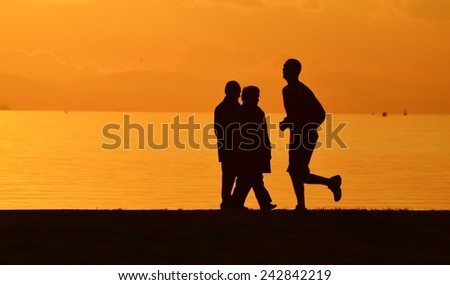 Man running on seashore at sunset, silhouette.