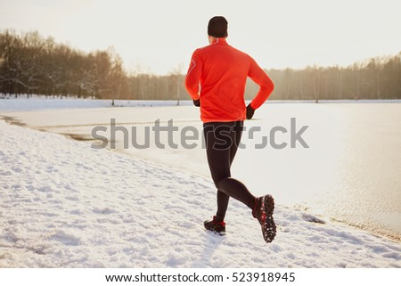 Man running on snow during cold winter