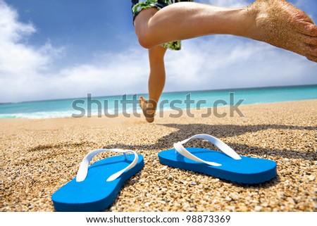man running on the beach and slipper - stock photo