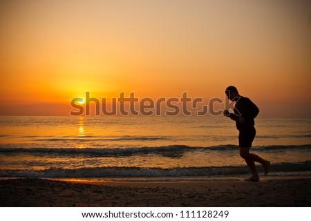 Man running on the beach at sunrise - stock photo