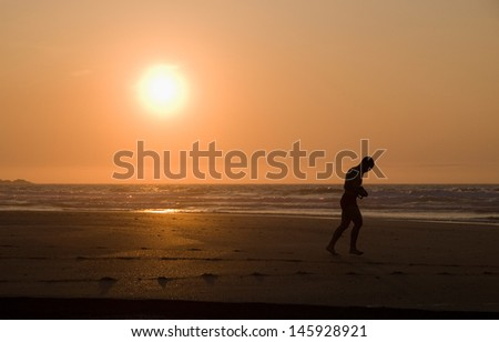 Man running on the beach at sunset in Galicia, Spain. - stock photo