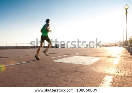 Man running on the promenade at the seaside. Motion blur on the runner, a lot of copy space (Nice, France, Europe). - stock photo