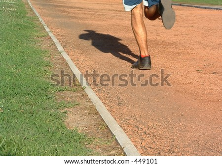 man running on the racetrak (only legs visible) - stock photo