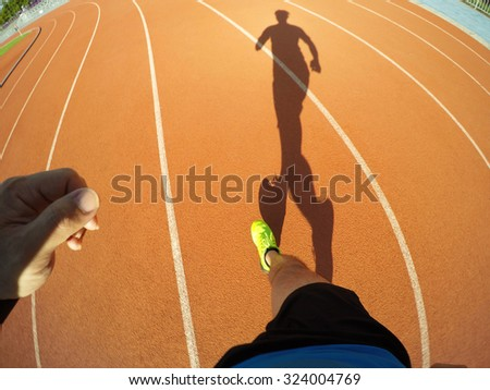 Man running on track, movement  shot.