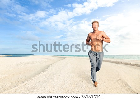 Man running on white sand of tropical beach - stock photo