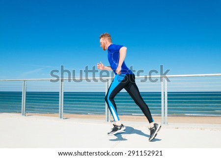 Man running or jogging at a beachside park. - stock photo