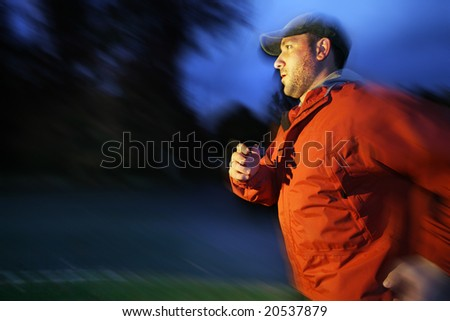 Man running outdoors at twilight, blurred motion. - stock photo