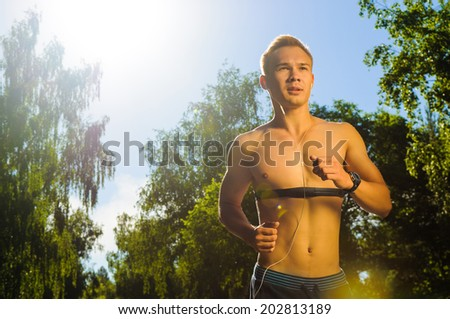 Man running outdoors during morning sunlight - stock photo