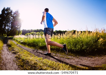 Man running outdoors during sunset - stock photo