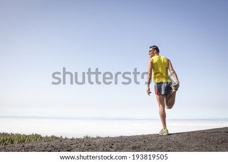 Man running outdoors, Male runner training for marathon run - stock photo