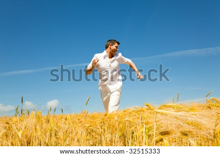 Man running through a golden corn field with blue sky as symbol of insurance
