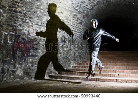 Man running trough dungeon, jumping with shadow on the wall - stock photo