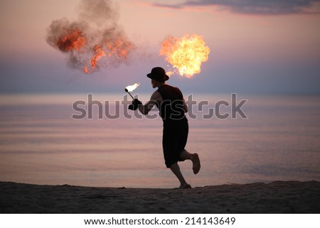 Man running with fire torch - stock photo