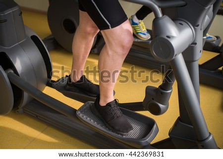 man runs on a treadmill, exercise in the sport club - stock photo