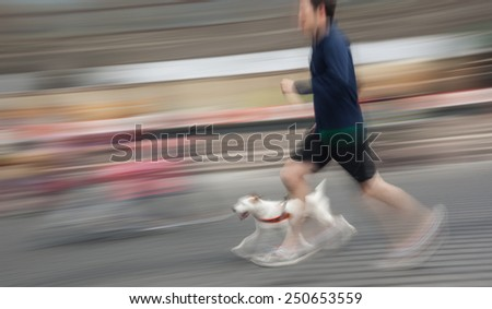 Man runs with his dog outside. Intentional motion blur - stock photo