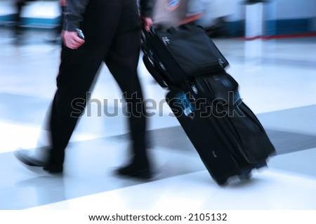 Man rushing through an airport terminal - stock photo